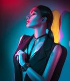 Πορτρέτο της προκλητικής γυναίκας στα μαύρα ενδύματα, εξαρτήματα μόδας, φωτεινό makeup στο φως νέου Στοκ Εικόνες