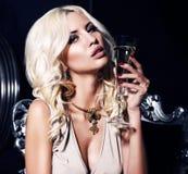 Πορτρέτο της προκλητικής γυναίκας με τα ξανθά μαλλιά με το ποτήρι της σαμπάνιας Στοκ Φωτογραφία