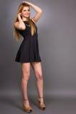 Πορτρέτο της προκλητικής νέας ξανθής γυναίκας που φορά ένα μίνι μαύρο φόρεμα Στοκ Εικόνες