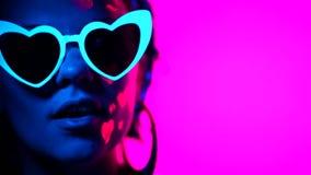 Πορτρέτο της πρότυπης γυναίκας μόδας με διαμορφωμένα τα καρδιά γυαλιά στο φως νέου Φθορισμού ασυνήθιστο makeup που καίγεται κάτω  απόθεμα βίντεο