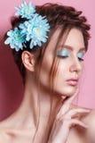 Πορτρέτο της ρομαντικής νέας γυναίκας με το μπλε λουλούδι που εξετάζει τη κάμερα στο μπλε υπόβαθρο Φωτογραφία μόδας άνοιξη Έμπνευ Στοκ φωτογραφίες με δικαίωμα ελεύθερης χρήσης