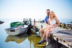 Πορτρέτο της ρομαντικής νέας όμορφης συνεδρίασης ζευγών στην αποβάθρα Στοκ φωτογραφία με δικαίωμα ελεύθερης χρήσης