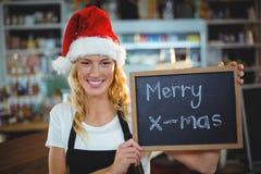 Πορτρέτο της σερβιτόρας που παρουσιάζει πίνακα κιμωλίας με το εύθυμο σημάδι Χριστουγέννων Στοκ φωτογραφία με δικαίωμα ελεύθερης χρήσης