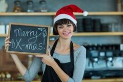 Πορτρέτο της σερβιτόρας που παρουσιάζει πλάκα με το εύθυμο σημάδι Χριστουγέννων Στοκ φωτογραφία με δικαίωμα ελεύθερης χρήσης