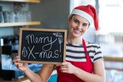 Πορτρέτο της σερβιτόρας που παρουσιάζει πλάκα με το εύθυμο σημάδι Χριστουγέννων Στοκ Φωτογραφία