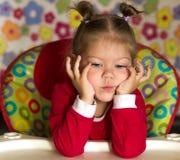Πορτρέτο της σκέψης και του λυπημένου propping κεφαλιού μικρών κοριτσιών με το χέρι στοκ εικόνα