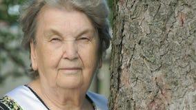 Πορτρέτο της σοβαρής ηλικιωμένης ηλικιωμένης γυναίκας στο δάσος φιλμ μικρού μήκους