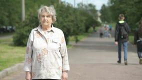 Πορτρέτο της σοβαρής ηλικιωμένης γυναίκας στο πάρκο φιλμ μικρού μήκους