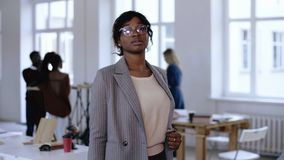 Πορτρέτο της σοβαρής νέας αφρικανικής επιχειρησιακής γυναίκας επιχειρηματιών eyeglasses και της επίσημης τοποθέτησης κοστουμιών σ φιλμ μικρού μήκους