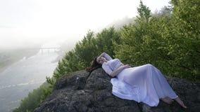 Πορτρέτο της στοχαστικής νέας νύφης που βρίσκεται στους βράχους μόνο με τις προσοχές ιδιαίτερες Ποταμός στην ομίχλη στο υπόβαθρο Στοκ φωτογραφίες με δικαίωμα ελεύθερης χρήσης