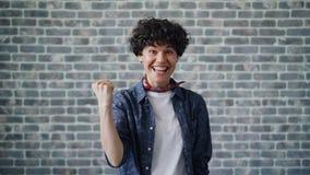 Πορτρέτο της συγκινημένης νέας γυναίκας που αυξάνει τις πυγμές που γιορτάζουν την επιτυχία και την τύχη φιλμ μικρού μήκους