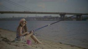 Πορτρέτο της συνεδρίασης κοριτσιών χαμόγελου στην τράπεζα και αλιεία απόθεμα βίντεο