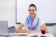 Πορτρέτο της συνεδρίασης δασκάλων χαμόγελου στο γραφείο στην τάξη Στοκ φωτογραφίες με δικαίωμα ελεύθερης χρήσης