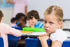Πορτρέτο της λυπημένης συνεδρίασης μαθητριών στην τάξη στοκ εικόνες