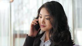 Πορτρέτο της χαμογελώντας ασιατικής επιχειρηματία που έχει τη συνομιλία που μιλά χρησιμοποιώντας το smartphone απόθεμα βίντεο