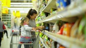 Πορτρέτο της χαμογελώντας γυναίκας και του κοριτσιού που επιλέγουν τα προϊόντα στο κατάστημα τροφίμων Mom και κόρη που βάζουν μερ φιλμ μικρού μήκους