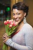Πορτρέτο της χαμογελώντας γυναίκας με τις τουλίπες στοκ εικόνα με δικαίωμα ελεύθερης χρήσης