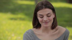 Πορτρέτο της χαμογελώντας ευτυχούς νέας γυναίκας σε ένα πάρκο φιλμ μικρού μήκους