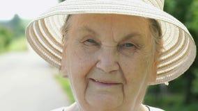 Πορτρέτο της χαμογελώντας ηλικιωμένης γυναίκας που ντύνεται στο καπέλο απόθεμα βίντεο