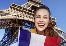 Πορτρέτο της χαμογελώντας νέας γυναίκας που παρουσιάζει σημαία στο Παρίσι, Γαλλία Στοκ Εικόνα