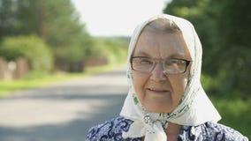 Πορτρέτο της χαμογελώντας ώριμης ηλικιωμένης γυναίκας στα γυαλιά απόθεμα βίντεο