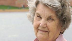 Πορτρέτο της χαμογελώντας ώριμης ηλικιωμένης γυναίκας υπαίθρια φιλμ μικρού μήκους