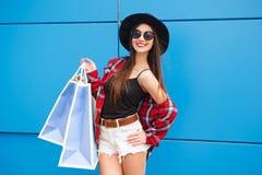 Πορτρέτο της χαμογελώντας γυναίκας μόδας ομορφιάς με τις τσάντες αγορών στα γυαλιά ηλίου στο μπλε υπόβαθρο υπαίθριος Copyspace Στοκ Φωτογραφία