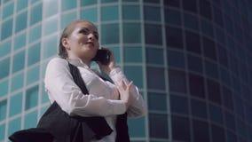 Πορτρέτο της χαμογελώντας επιχειρησιακής γυναίκας που στέκεται υπαίθρια και που διοργανώνει μια ευχάριστη τηλεφωνική συζήτηση φιλμ μικρού μήκους