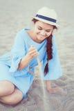 Πορτρέτο της χαμογελώντας λευκιάς καυκάσιας γυναίκας brunette με το μαυρισμένο δέρμα στην μπλε συνεδρίαση καπέλων φορεμάτων και α Στοκ φωτογραφία με δικαίωμα ελεύθερης χρήσης