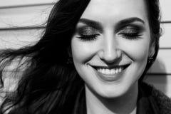 Πορτρέτο της χαμογελώντας Ευρωπαίας γυναίκας με τις ιδιαίτερες προσοχές, τη μακριά σκοτεινή τρίχα, τα αισθησιακά χείλια και επαγγ Στοκ Φωτογραφία