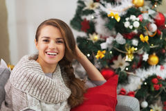 Πορτρέτο της χαμογελώντας νέας γυναίκας κοντά στο χριστουγεννιάτικο δέντρο Στοκ Εικόνες