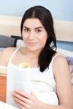 Πορτρέτο της χαμογελώντας νέας γυναίκας που διαβάζει ένα βιβλίο Στοκ φωτογραφίες με δικαίωμα ελεύθερης χρήσης