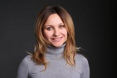 Πορτρέτο της χαμογελώντας νέας γυναίκας στο μαύρο κλίμα στο στούντιο Στοκ Εικόνες