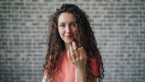 Πορτρέτο της χαριτωμένης άνεμος τρίχας γυναικών γύρω από το φλερτ δάχτυλων που εξετάζει τη κάμερα φιλμ μικρού μήκους