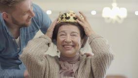 Πορτρέτο της χαριτωμένης αρκετά ώριμης γυναίκας Ο ενήλικος εγγονός φέρνει την κορώνα και την βάζει στο κεφάλι της γιαγιάς, ανώτερ απόθεμα βίντεο