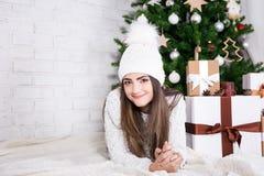 Πορτρέτο της χαριτωμένης γυναίκας που εναπόκειται διακοσμημένη δώρων πλησίον στα Χριστούγεννα Στοκ Εικόνες