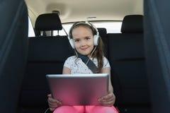 Πορτρέτο της χαριτωμένης μουσικής ακούσματος κοριτσιών στο ακουστικό από την ψηφιακή ταμπλέτα Στοκ φωτογραφίες με δικαίωμα ελεύθερης χρήσης