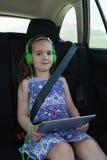 Πορτρέτο της χαριτωμένης μουσικής ακούσματος κοριτσιών στο ακουστικό από την ψηφιακή ταμπλέτα Στοκ Εικόνες