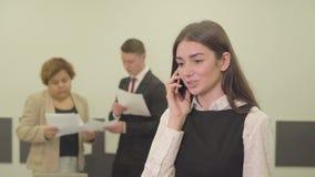 Πορτρέτο της χαριτωμένης νέας γυναίκας στην επίσημη ένδυση που μιλά από το κινητό τηλέφωνο στο πρώτο πλάνο στο γραφείο ενώ το αρσ φιλμ μικρού μήκους
