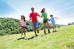 Πορτρέτο της χαρούμενης οικογένειας που τρέχει στη φύση Στοκ Φωτογραφία