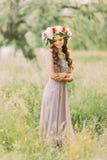 Πορτρέτο της όμορφης γοητευτικής νέας κυρίας στο στεφάνι λουλουδιών και το άσπρο ιώδες φόρεμα που κοιτάζει κάτω στοκ εικόνες με δικαίωμα ελεύθερης χρήσης