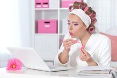 Πορτρέτο της όμορφης γυναίκας με τα ρόλερ τρίχας που εξετάζουν το lap-top στοκ εικόνες