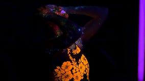Πορτρέτο της όμορφης γυναίκας με την πορφυρή τρίχα που χορεύει με το λαμπτήρα UV φωτός νέου Πρότυπο κορίτσι με φθορισμού δημιουργ απόθεμα βίντεο