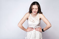 Πορτρέτο της όμορφης γυναίκας με τις φακίδες και του λευκού έξυπνου ρολογιού φορεμάτων και με τον πόνο στομαχιών στο ασημένιο γκρ στοκ φωτογραφίες με δικαίωμα ελεύθερης χρήσης