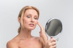 Πορτρέτο της όμορφης γυναίκας που εξετάζει τον καθρέφτη Στοκ Φωτογραφία