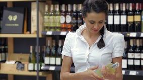 Πορτρέτο της όμορφης γυναίκας που εξετάζει το μπουκάλι κρασιού απόθεμα βίντεο