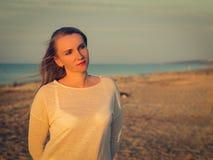 Πορτρέτο της όμορφης γυναίκας στα άσπρα ενδύματα στην παραλία Στοκ Εικόνα