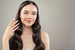 Πορτρέτο της όμορφης γυναίκας brunette με το υγιές δέρμα και της τρίχας στο γκρίζο υπόβαθρο στοκ εικόνες