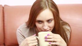 Πορτρέτο της όμορφης γυναίκας oung με ένα φλυτζάνι στον καναπέ απόθεμα βίντεο