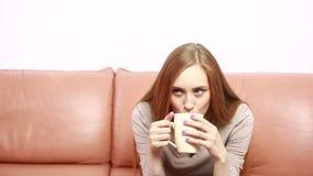Πορτρέτο της όμορφης γυναίκας oung με ένα φλυτζάνι στον καναπέ φιλμ μικρού μήκους